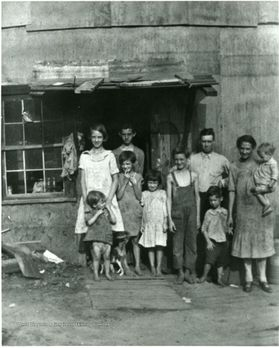 A group of people, including children, stand outside a building
